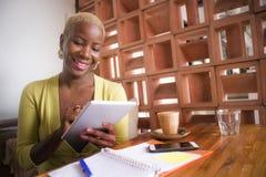 Молодая элегантная и красивая черная Афро-американская работа бизнес-леди онлайн с цифровой пусковой площадкой таблетки на кофейн стоковые фотографии rf