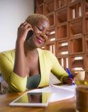 Молодая элегантная и красивая черная Афро-американская работа бизнес-леди онлайн с мобильным телефоном на кофейне принимая примеч Стоковое Фото
