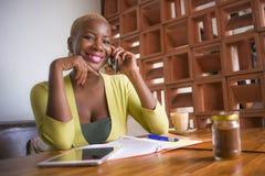 Молодая элегантная и красивая черная Афро-американская работа бизнес-леди онлайн с мобильным телефоном на усмехаться кофейни счас Стоковое Изображение RF