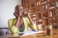 Молодая элегантная и красивая черная Афро-американская работа бизнес-леди онлайн с мобильным телефоном на усмехаться кофейни счас Стоковое Изображение