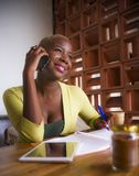 Молодая элегантная и красивая черная Афро-американская работа бизнес-леди онлайн с мобильным телефоном на кофейне принимая примеч Стоковое фото RF