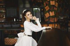 Молодая элегантная красивая и сексуальная женщина модели брюнет в белом платье при золотой пояс сидя в баре и ждать стоковые фото