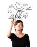 Молодая электрическая лампочка чертежа женщины дела с различными диаграммами стоковое фото