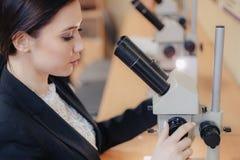 Молодая эмоциональная привлекательная девушка сидя на таблице и работая с микроскопом в современных офисе или аудитории стоковое фото