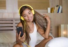Молодая этничность красивой и счастливой женщины студента азиатская латинская смешала слушать к музыке с наушниками в кровати поя Стоковое Фото