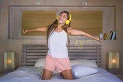 Молодая этничность красивой и счастливой женщины студента азиатская латинская смешала слушать к музыке с наушниками в кровати поя Стоковые Изображения RF