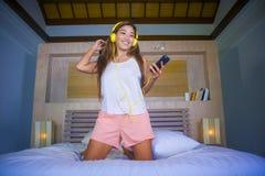 Молодая этничность красивой и счастливой женщины студента азиатская латинская смешала слушать к музыке с наушниками в кровати поя Стоковая Фотография RF