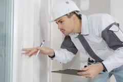 Молодая builderchecking стена в строительной площадке стоковые изображения rf