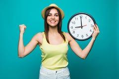 Молодая excited женщина держа часы показывая почти 9 с счастливыми эмоциями победы на зеленой предпосылке стоковые изображения rf