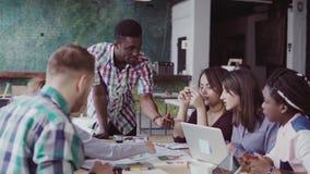 Молодая multiracial группа людей работая в coworking космосе Малый запуск архитекторов обсуждая идеи проекта акции видеоматериалы