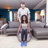 Молодые пары тренируют делающ гимнастику дома стоковые фотографии rf
