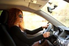 Молодая red-haired женщина управляя автомобилем стоковое изображение rf