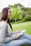 Молодая relaxed девушка смотря отсутствующим пока не держащ ее ручку и ее никакое Стоковое Изображение RF