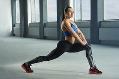 Молодая sporty девушка при атлетическое тело делая радиоактивные осадки в спортзале Стоковые Фото