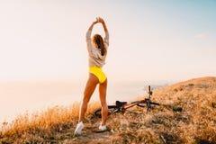Молодая sporty женщина в желтых одеждах и в белых тапках с горным велосипедом в природе Стоковые Фото
