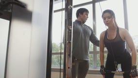 Молодая sporty женщина делая тренировку фитнеса силы на спортзале спорта - тренер помогает ей Стоковая Фотография