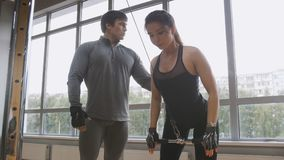 Молодая sporty женщина делая тренировку фитнеса силы на спортзале спорта - тренер помогает ей Стоковые Фотографии RF