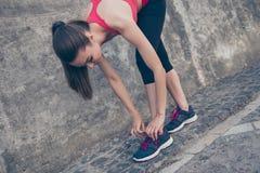 Молодая sporty женщина связывает шнурки идущих ботинок перед traini Стоковое Изображение
