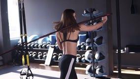 Молодая sporty женщина тренирует мышцы рук и назад использует резиновые ленты Она tensing мышцы, стоя назад к сток-видео