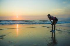 Молодая sporty и утомленная Афро-американская женщина бегуна охлаждая дышать вымотанный после идущей разминки на красивых солнцах стоковое изображение rf