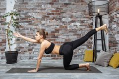 Молодая sporty тонкая женщина делая тренировку йоги дома протягивая ее руку к фронту Стоковые Изображения RF