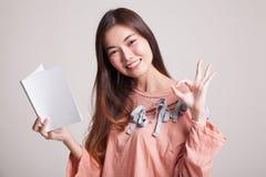 Молодое азиатское О'КЕЙ выставки женщины с книгой Стоковое Фото