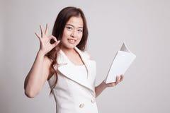 Молодое азиатское О'КЕЙ выставки женщины с книгой Стоковые Изображения RF