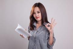 Молодое азиатское О'КЕЙ выставки женщины с книгой Стоковое фото RF