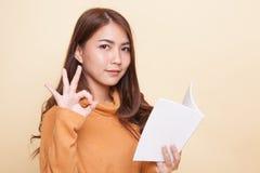 Молодое азиатское О'КЕЙ выставки женщины с книгой Стоковое Изображение