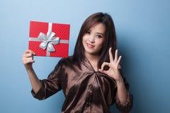 Молодое азиатское О'КЕЙ выставки женщины с подарочной коробкой Стоковые Изображения RF