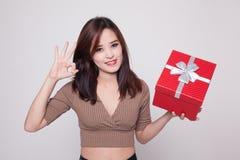 Молодое азиатское О'КЕЙ выставки женщины с подарочной коробкой Стоковые Фотографии RF