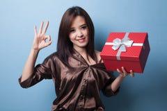 Молодое азиатское О'КЕЙ выставки женщины с подарочной коробкой Стоковое Изображение RF