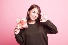 Молодое азиатское О'КЕЙ выставки женщины с подарочной коробкой Стоковая Фотография