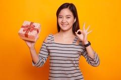 Молодое азиатское О'КЕЙ выставки женщины с подарочной коробкой Стоковое фото RF