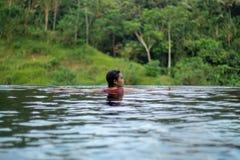 Молодое азиатское плавание девушки в пейзажном бассейне с красивым видом Ей принимают фото от задней части стоковое фото