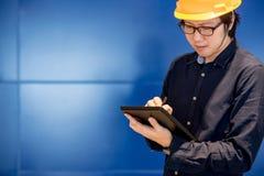 Молодое азиатское сочинительство человека инженера на таблетке Стоковая Фотография RF