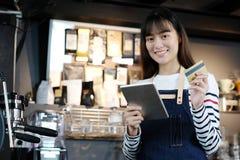 Молодое азиатское barista женщины используя таблетку и кредитную карточку a держать Стоковые Изображения