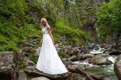 Молодое белокурое положение девушки в полу-повороте и смотреть вниз на кромке платья будуара в горах против водопада стоковые изображения rf