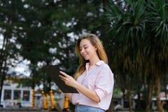 Молодое белокурое сочинительство коммерсантки снаружи, носящ блузку Стоковая Фотография RF