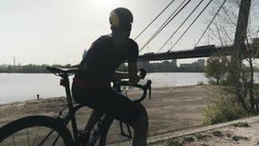 Молодое бородатое triathlete в черном jersey и шорты думая и мечтая смотреть к реке города, мосту Triathlete ? blac акции видеоматериалы