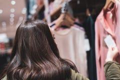 Молодое брюнет выбирает одежды весны женщина ног принципиальной схемы мешка предпосылки ходя по магазинам белая стоковые фото