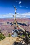 Молодое Гай сидя на краю гранд-каньона стоковое фото rf