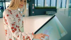 Молодое женское ища правильное направление на доске навигации в современном торговом центре сток-видео