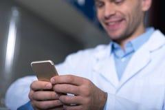 Молодое занятое усаживание практикующий врача и использование его мобильного телефона стоковые фотографии rf