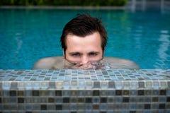 Молодое кавказское заплывание человека и скрываться на летних каникулах на бассейне Половинный головной надводный преследовать Стоковая Фотография RF