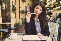 Молодое катание бизнес-леди и подписывает внутри документы на кафе Стоковое Изображение RF