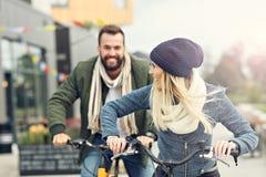 Молодое катание пар велосипед и имеющ потеху в городе Стоковая Фотография RF