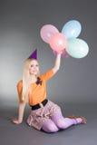 Молодое красивейшее белокурое усаживание над серым цветом с воздушными шарами Стоковое Фото