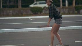 Молодое красивое женское катание битника на улице на скейтборде или longboard на дне