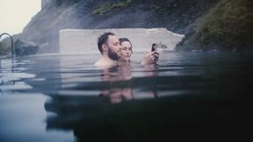 Молодое красивое плавание пар в горячих источниках в Исландии Путешествовать человек и женщина принимая фото selfie на смартфоне акции видеоматериалы
